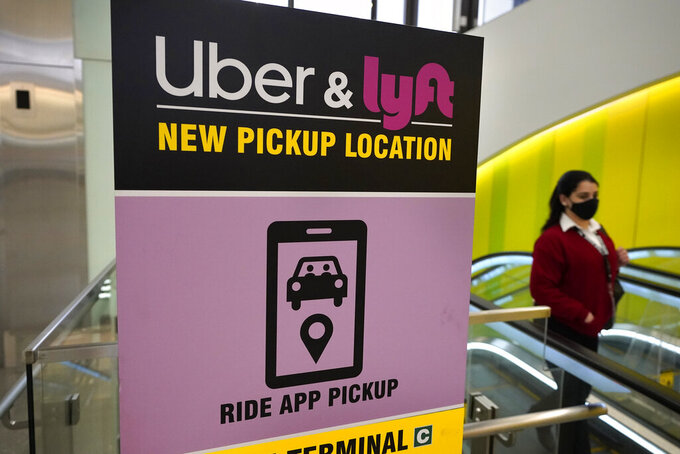 A passer-by walks past a sign offering directions to an Uber and Lyft ride pickup location at Logan International Airport, in Boston, Tuesday, Feb. 9, 2021. Uber and Lyft are taking different routes around the roadblock the virus pandemic dropped on their paths to profitability. The companies have racked up tens of billions of dollars in losses since starting up, and the slump in passenger activity has pushed profitability ever further off into the future.  (AP Photo/Steven Senne)