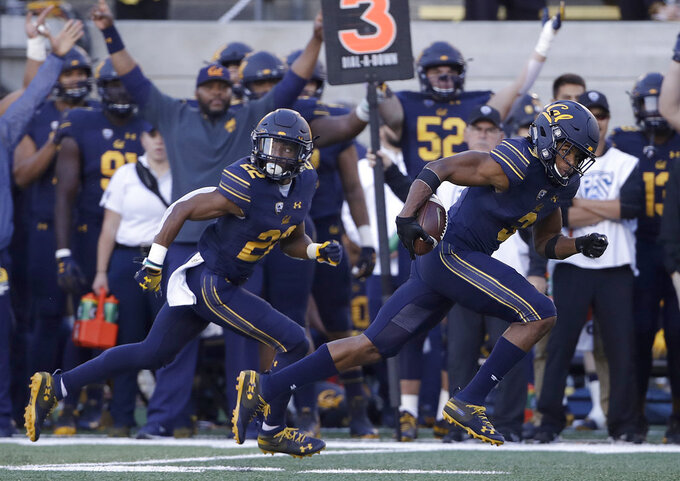 California cornerback Elijah Hicks, right, returns an interception for a touchdown against Colorado during the first half of an NCAA college football game in Berkeley, Calif., Saturday, Nov. 24, 2018. (AP Photo/Jeff Chiu)
