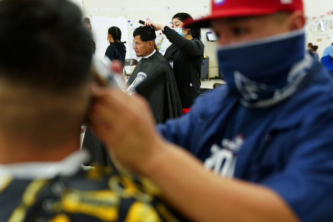 Migrant men get haircuts at a migrant shelter, Wednesday, May 12, 2021, in McAllen, Texas. The U.S. government continues to report large numbers of migrants crossing the U.S.-Mexico border with an increase in adult crossers. But families and unaccompanied children are still arriving in dramatic numbers despite the weather changing in the Rio Grande Valley registering hotter days and nights. (AP Photo/Gregory Bull)