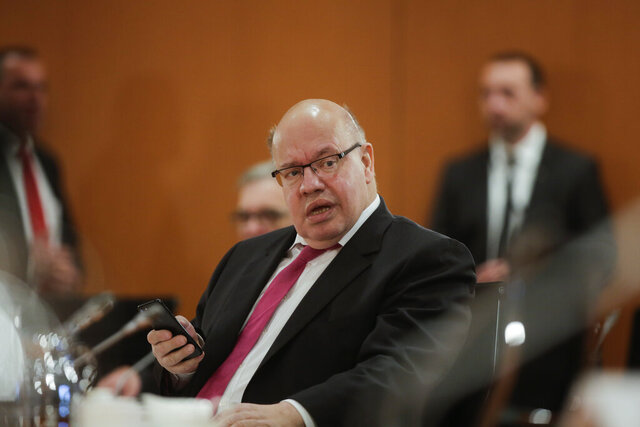 German Economy Minister Peter Altmaier makes a phone call prior to the weekly cabinet meeting of the German government at the chancellery in Berlin, Germany, Wednesday, April 8, 2020. In order to slow down the spread of the coronavirus, the German government has considerably restricted public life and asked the citizens to stay at home. The new coronavirus causes mild or moderate symptoms for most people, but for some, especially older adults and people with existing health problems, it can cause more severe illness or death.(AP Photo/Markus Schreiber, Pool)