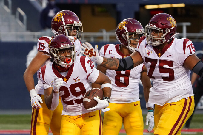 Southern California running back Vavae Malepeai (29) celebrates with teammates after scoring a touchdown against Arizona during the second half of an NCAA college football game Saturday, Nov. 14, 2020, in Tucson, Ariz. Southern California won 34-30. (AP Photo/Rick Scuteri)