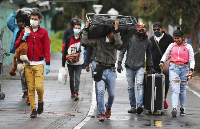 Venezuelan migrants leave on foot toward the Venezuelan border, with the aim of leaving Colombia after a lockdown ordered by the government in an effort to prevent the spread of the new coronavirus, in Bogota, Colombia, Monday, April 6, 2020. Many Venezuelans in Colombia say they have not been able to find work in a country where businesses remain shuttered and people have been ordered to stay inside because of the coronavirus pandemic. (AP Photo/Fernando Vergara)