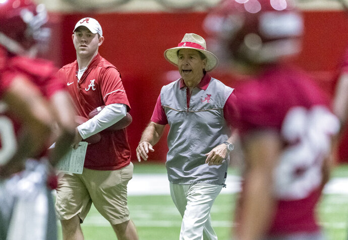 """FILE - In this March 20, 2018, file photo, Alabama coach Nick Saban works with defensive backs during drills at the NCAA college football team's spring practice in Tuscaloosa, Ala. Saban doesn't believe extending preseason camp for college football teams around the country is necessarily the best way to get them ready for the season. Saban said Thursday, April 2, 2020, that he'd prefer some """"teaching sessions on the field"""" over the summer to prepare for camp, even if it is in shorts and T-shirts. The coronavirus pandemic led to the cancellation of spring sports, including football practices, across the nation. (Vasha Hunt/AL.com via AP, File)"""
