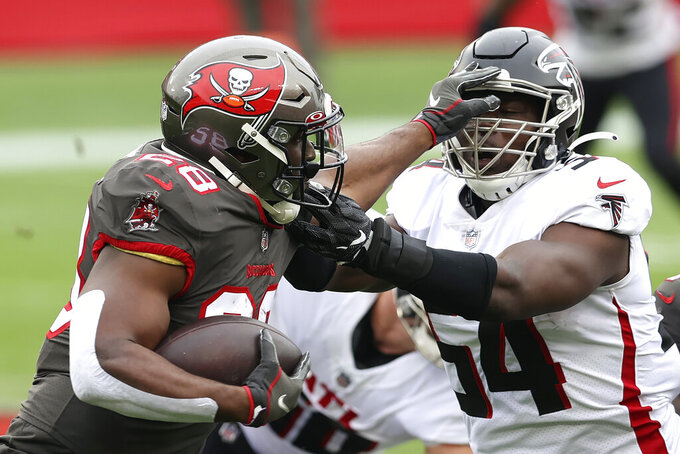Tampa Bay Buccaneers running back Leonard Fournette (28) stiff arms Atlanta Falcons linebacker Foye Oluokun (54) on a run during the first half of an NFL football game Sunday, Jan. 3, 2021, in Tampa, Fla. (AP Photo/Mark LoMoglio)