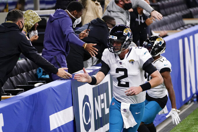 Jacksonville Jaguars quarterback Mike Glennon (2) celebrates a touchdown with fans during the first half of an NFL football game against the Indianapolis Colts, Sunday, Jan. 3, 2021, in Indianapolis. (AP Photo/AJ Mast)