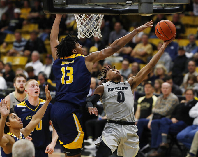 UC Irvine forward Austin Johnson (13) goes up to block a shot by Colorado guard Shane Gatling (0) in the second half of an NCAA college basketball game Monday, Nov. 18, 2019, in Boulder, Colo.  (AP Photo/David Zalubowski)