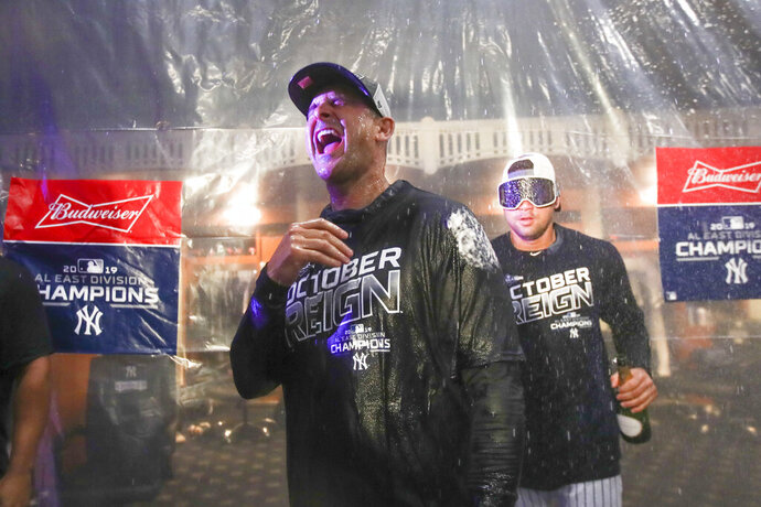 Players spray New York Yankees manager Aaron Boone as they celebrate after defeating the Los Angeles Angels and clinching the AL East title with a 9-1 win in a baseball game Thursday, Sept. 19, 2019, in New York. (AP Photo/Mary Altaffer)