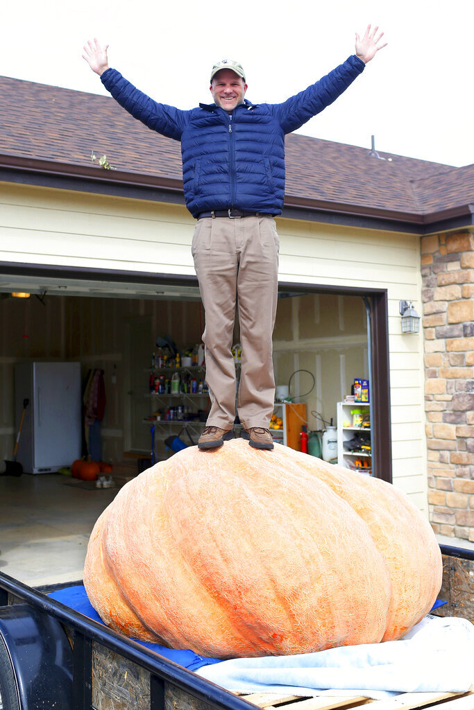 In this Wednesday, Oct. 16, 2019 photo Andy Corbin poses for a photo with his 1,491 pound pumpkin in Cheyenne. Corbin now once again holds the state record for largest pumpkin. (Michael Cummo/The Wyoming Tribune Eagle via AP)