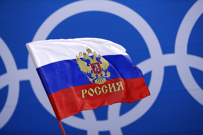 FILE - In this Saturday, Feb. 17, 2018 file photo Russian supporter waves a flag before the preliminary round of the men's hockey game between the team from Russia and the United States at the 2018 Winter Olympics in Gangneung, South Korea. Russia was banned Thursday Dec. 17, 2020 from using its name, flag and anthem at the next two Olympics or at any world championships for the next two years. The Court of Arbitration for Sport's ruling also blocked Russia from bidding to host major sporting events for two years. (AP Photo/Matt Slocum, File)