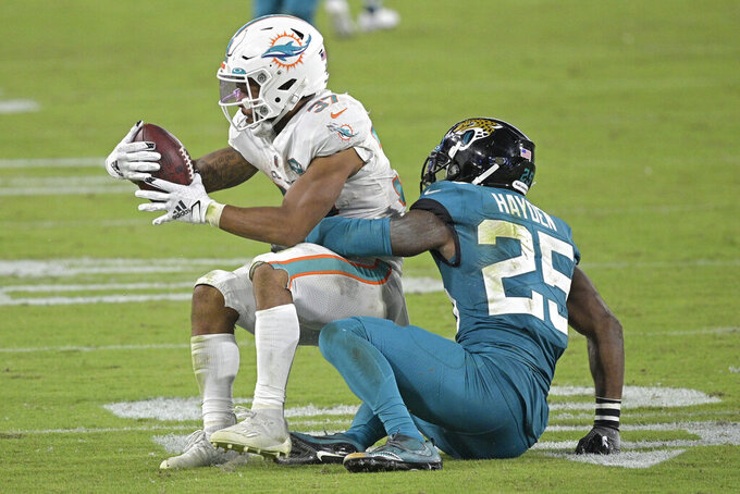 Miami Dolphins running back Myles Gaskin (37) is stopped by Jacksonville Jaguars cornerback D.J. Hayden (25) during the second half of an NFL football game, Thursday, Sept. 24, 2020, in Jacksonville, Fla. (AP Photo/Phelan M. Ebenhack)