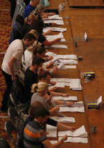 Official counters sort votes cast into different piles during counting for the European Elections for the South East England region, in Southampton, England, Sunday, May 26, 2019. (AP Photo/Alastair Grant)