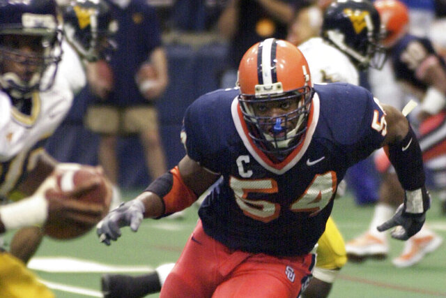 FILE - In this Nov. 10, 2001, file photo, Syracuse defensive end Dwight Freeney (54) bares down on West Virginia quarterback Rasheed Marshall during the fourth quarter of an NCAA college football game, in Syracuse, N.Y. Georgia cornerback Champ Bailey, Syracuse defensive end Dwight Freeney and Kansas State running back Darren Sproles will appear on the College Hall of Fame ballot for the first time. The National Football Foundation announced Tuesday, June 16, 2020, the 78 players and seven coaches from major college who are up for selection to the Hall of Fame. (AP Photo/Kevin Rivoli, File)