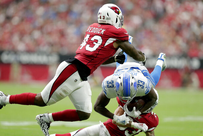 Detroit Lions running back Kerryon Johnson (33) is hit by Arizona Cardinals outside linebacker Haason Reddick (43) and cornerback Robert Alford during the first half of an NFL football game, Sunday, Sept. 8, 2019, in Glendale, Ariz. (AP Photo/Darryl Webb)