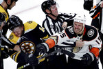 Anaheim Ducks center Ryan Getzlaf (15) grapples with Boston Bruins right wing Chris Wagner (14) as linesman Matt MacPherson (83) tries to break up the fight in the third period of an NHL hockey game, Monday, Oct. 14, 2019, in Boston. (AP Photo/Elise Amendola)