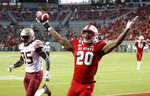 North Carolina State's Ricky Person Jr. (20) celebrates after he scored a touchdown against Florida State's Leonard Warner III (35) during the second half of an NCAA college football game in Raleigh, N.C., Saturday, Nov. 3, 2018. (AP Photo/Chris Seward)