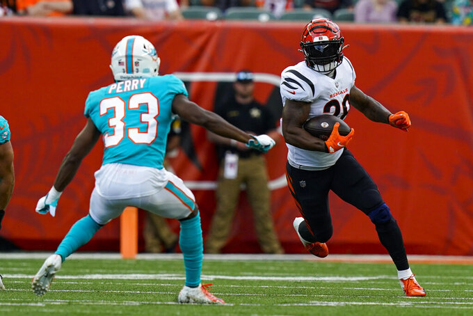 Cincinnati Bengals running back Joe Mixon (28) cuts around Miami Dolphins cornerback Jamal Perry (33) during the first half of an NFL exhibition football game in Cincinnati, Sunday, Aug. 29, 2021. (AP Photo/Bryan Woolston)