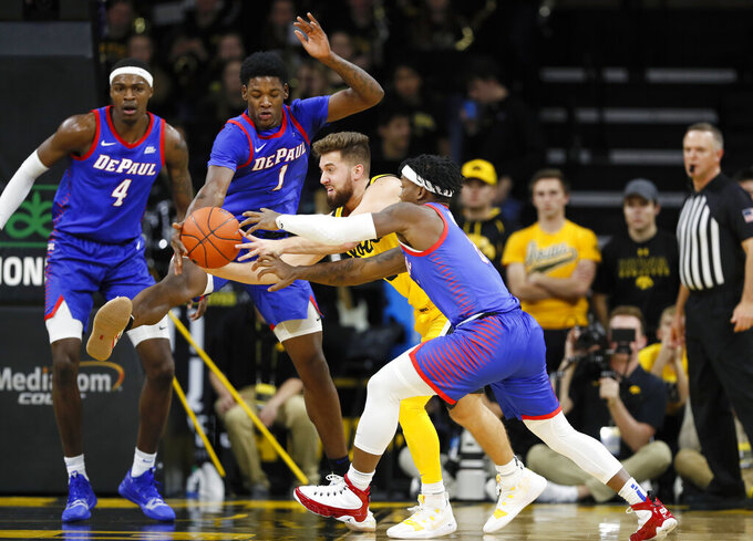 Iowa guard Jordan Bohannon, center, drives between DePaul's Romeo Weems (1) and Markese Jacobs, right, during the first half of an NCAA college basketball game, Monday, Nov. 11, 2019, in Iowa City, Iowa. (AP Photo/Charlie Neibergall)