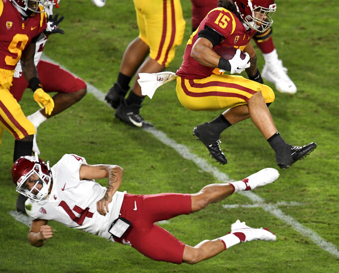 Southern California safety Talanoa Hufanga (15) leaps over Washington State quarterback Jayden de Laura (4) after intercepting a pass in the first half of an NCAA college football game in Los Angeles, Sunday, Dec. 6, 2020. (Keith Birmingham/The Orange County Register via AP)