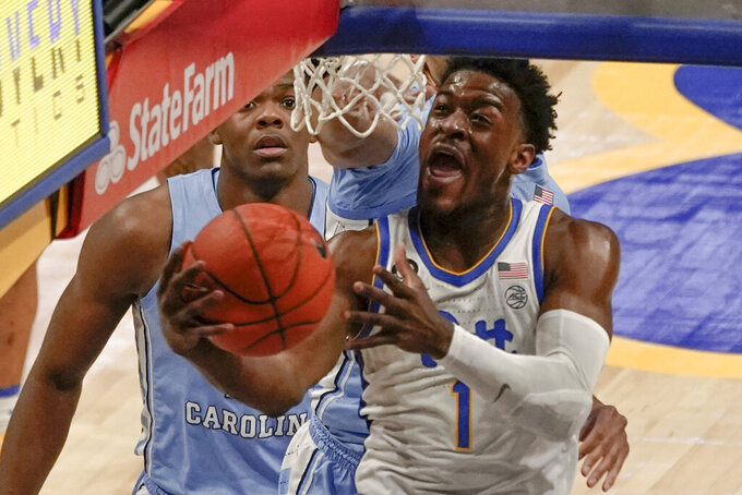 Pittsburgh's Xavier Johnson (1) shoots after getting by North Carolina's Day'Ron Sharpe, left, and Garrison Brooks during the first half of an NCAA college basketball game Tuesday, Jan. 26, 2021, in Pittsburgh. (AP Photo/Keith Srakocic)