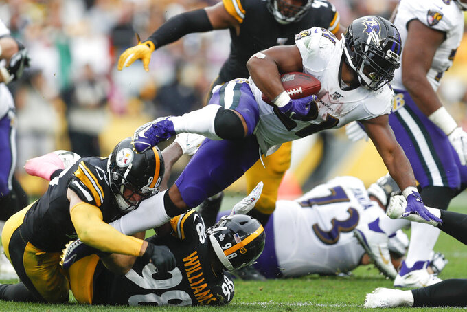 Baltimore Ravens running back Mark Ingram (21) is hit by Pittsburgh Steelers linebackers T.J. Watt (90) and Vince Williams on a run in the second half of an NFL football game, Sunday, Oct. 6, 2019, in Pittsburgh. The Ravens won 26-23. (AP Photo/Don Wright)