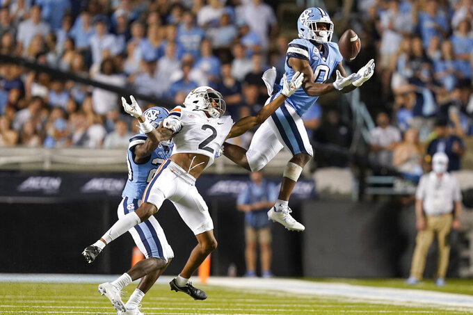 North Carolina defensive back Ja'Qurious Conley (0) intercepts a pass over Virginia wide receiver Ra'Shaun Henry (2) during the second half of an NCAA college football game in Chapel Hill, N.C., Saturday, Sept. 18, 2021. (AP Photo/Gerry Broome)