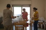 Basma Mostafa, a 30-year-old journalist who founded an initiative that sends freshly home cooked meals to quarantined coronavirus patients, center, and Fatma Youssef, a volunteer, right, package food into boxes, at an apartment, in Cairo, Egypt. Saturday, July 11, 2020. Volunteers in Egypt hope the meals will help nurse quarantined coronavirus patients back to health and provide them with some respite. In different neighborhoods in Cairo and some other cities they've enlisted people to cook, donate food or make contactless deliveries to patients' homes. (AP Photo/Nariman El-Mofty)