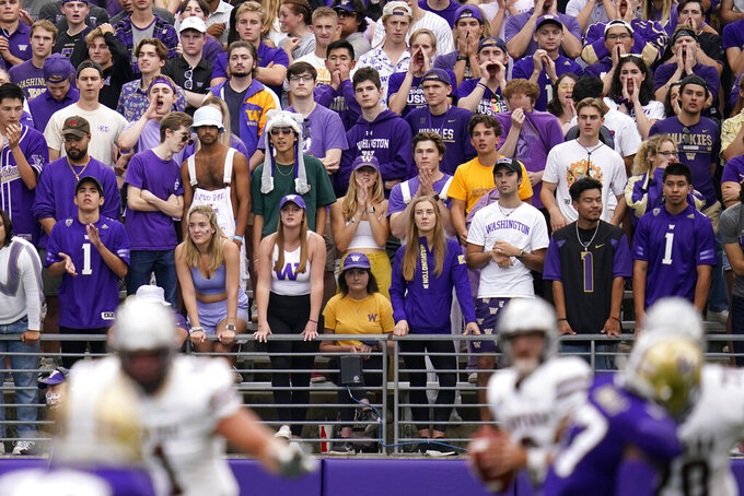Unmasked Washington fans look on from the student section in the first half of an NCAA college football game against Montana Saturday, Sept. 4, 2021, in Seattle. (AP Photo/Elaine Thompson)
