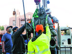 Workers fit straps to lift a statue of Spanish territorial governor Don Diego de Vargas from Cathedral Park on Thursday morning, June 18, 2020, in Santa Fe, N.M. Two other markers in the city were slated to come down as monuments to historical figures were being dismantled across the country. (Matt Dahlseid/Santa Fe New Mexican via AP)