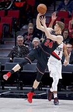 Chicago Bulls forward Lauri Markkanen, front, shoots over Portland Trail Blazers guard CJ McCollum during the first half of an NBA basketball game in Portland, Ore., Wednesday, Jan. 9, 2019. (AP Photo/Craig Mitchelldyer)