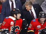 Calgary Flames' Milan Lucic is congratulated on his first goal as a Flame by interim coach Geoff Ward. as Sean Monahan smiles about it during the third period of an NHL hockey game against the Buffalo Sabres on Thursday, Dec. 5, 2019, in Calgary, Alberta. (Larry MacDougal/The Canadian Press via AP)