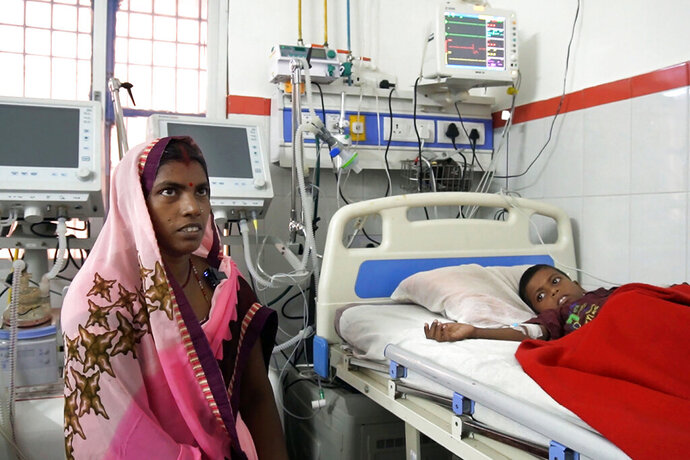 In this Sept. 13, 2019 photo, Pushpa Devi sits by the bed of her son Aryan Singh, 7, being treated for encephalitis at a hospital in Community Health Center in Chauri Chaurah in the northern Indian state of Uttar Pradesh. Cases of encephalitis, or inflammation of the brain, in Uttar Pradesh, India's most populated state with millions of rural poor, have dropped sharply. Doctors and state government officials credit a new network of rural clinics and a massive immunization and cleanliness drive in seven districts with the highest caseloads of the disease that's often deadly. An independent physician says there's no way to independently verify the government's claims, but that a decline is visible. (AP Photo/Usman Ahmad)