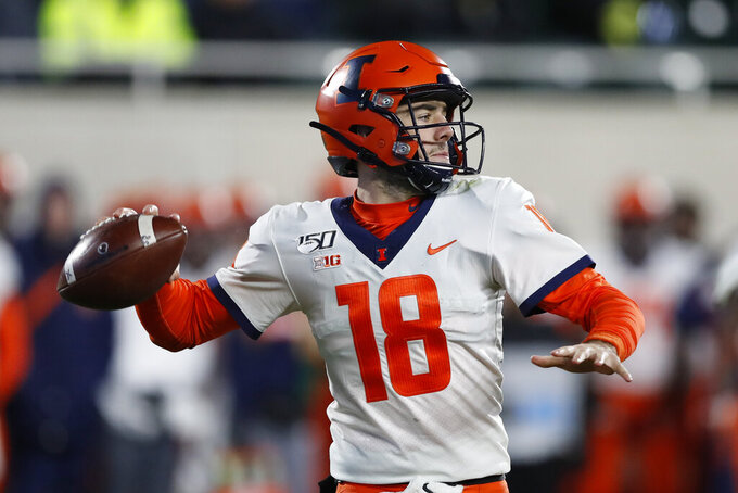 """FILE - In this Nov. 9, 2019, file photo, Illinois quarterback Brandon Peters throws during the second half of an NCAA college football game against Michigan State, in East Lansing, Mich. Even after beating a Wisconsin team that was favored by 30 ½ points last year, Illinois heads into Madison as a 19 ½-point underdog as the two West Division rivals prepare to open the pandemic-delayed Big Ten season Friday night. """"I guess we're going to have to go prove them wrong again,"""" Peters said. (AP Photo/Carlos Osorio, File)"""