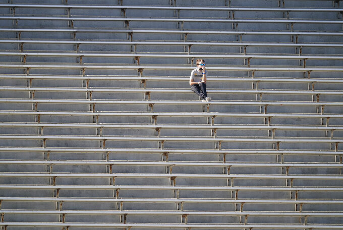 A fan watches from the stands during the first half of an NCAA college football game between Iowa and Michigan State, Saturday, Nov. 7, 2020, in Iowa City, Iowa. (AP Photo/Charlie Neibergall)