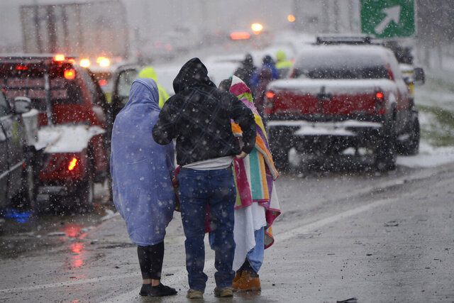 Motorists huddle together after a 54 car pile-up early morning on the Kennedy Expressway Wednesday, April 15, 2020, in Chicago.  The Chicago Fire Department says about 50 vehicles were involved in the pileup along the expressway. (AP Photo/Paul Beaty)
