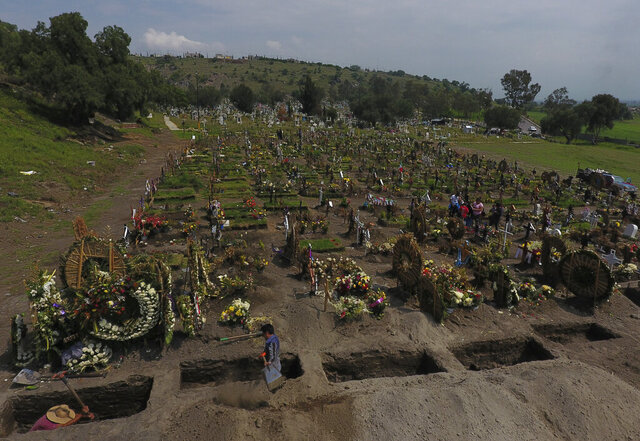Cemetery workers dig fresh graves in a section of the Valle de Chalco Municipal Cemetery which opened early in the coronavirus pandemic to accommodate the surge in deaths, in Valle de Chalco on the outskirts of Mexico City, Thursday, Sept. 24, 2020.(AP Photo/Rebecca Blackwell)
