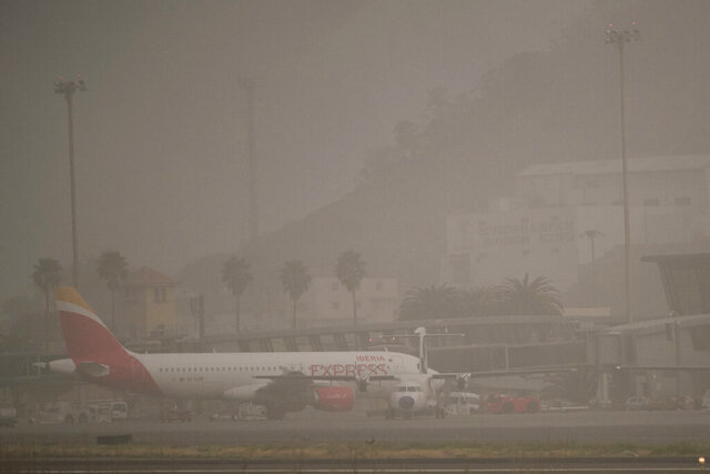 Passenger planes on the airport runway in Santa Cruz de Tenerife, Spain, Monday, Feb. 24, 2020. All airports on Spain's Canary Islands have reopened despite strong winds that are still bringing sand and dust from the Sahara desert, although the region's authorities said Monday that the worst was over. (AP Photo/Andres Gutierrez)