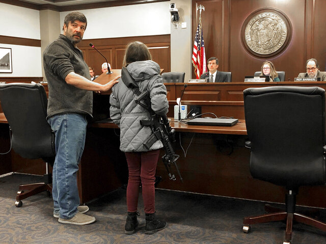 CORRECTS BYLINE TO KEITH RIDLER, NOT KEN RITTER - Charles Nielsen, 58, and his 11-year-old granddaughter, Bailey Nielsen, testify before a House panel at the Idaho Statehouse on Monday. Feb. 24, 2020 in Boise, Idaho. Visitors to Idaho 18 and older who can legally possess firearms would be allowed to carry a concealed handgun within city limits under legislation that headed to the House on Monday, Feb. 24.  (AP Photo/Keith Ridler)