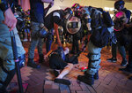 """Riot police detain protesters in Central, the main business district in Hong Kong, Sunday, Sept. 8, 2019.  Thousands of demonstrators in Hong Kong urge President Donald Trump to """"liberate"""" the semi-autonomous Chinese territory during a peaceful march to the U.S. consulate, but violence broke out later in the business and retail district after protesters vandalized subway stations, set fires and blocked traffic. (AP Photo/Vincent Yu)"""