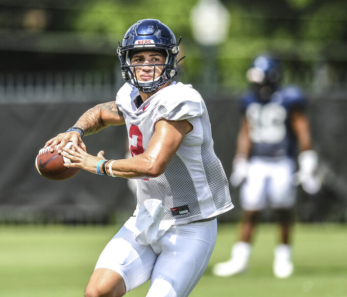 FILE - In this Aug. 5, 2019, file photograph, quarterback Matt Corral passes during Mississippi NCAA college football practice in Oxford, Miss. Corral is expected to help lead the team to a bowl-eligible season in the highly competitive SEC. (Bruce Newman/Oxford Eagle via AP, File)