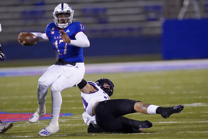 Kansas quarterback Jalon Daniels (17) is tackled by TCU linebacker Garret Wallow (30) during the first half of an NCAA college football game in Lawrence, Kan., Saturday, Nov. 28, 2020. (AP Photo/Orlin Wagner)
