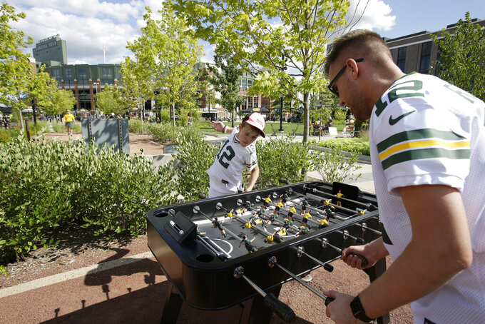 Fans play foosball in a park across from Lambeau Field prior to the start of a preseason NFL football game between the Green Bay Packers and Houston Texans Thursday, Aug. 8, 2019, in Green Bay, Wis. (AP Photo/Mike Roemer)