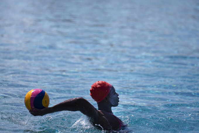 Ashleigh Johnson, a goalkeeper for U.S. women's water polo team, trains at MWR Aquatic Training Center in Los Alamitos, Calif., Tuesday, April 27, 2021. When the Tokyo Olympics was postponed because of the COVID-19 pandemic, U.S. women's water polo star Kiley Neushul decided to retire from the national team. The decision created a giant hole in the lineup for a powerhouse U.S. team going for a third consecutive gold medal this summer. (AP Photo/Jae C. Hong)