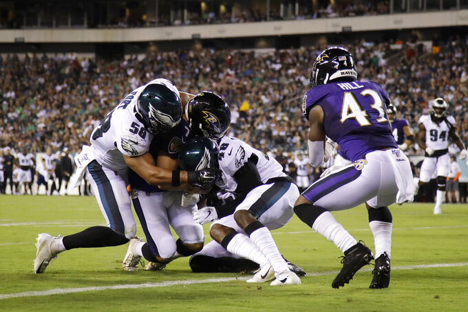 Baltimore Ravens' Trace McSorley (7) scores a touchdown against Philadelphia Eagles' L.J. Fort (58) and Josh Hawkins (48) during the first half of a preseason NFL football game Thursday, Aug. 22, 2019, in Philadelphia. (AP Photo/Matt Rourke)
