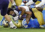 Washington running back Myles Gaskin, top, loses his helmet as he is tackled by UCLA linebacker Lokeni Toailoa (52) during the first half of an NCAA college football game Saturday, Oct. 6, 2018, in Pasadena, Calif. (AP Photo/Marcio Jose Sanchez)