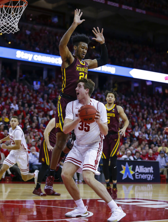 Wisconsin's Nate Reuvers (35) looks for a shot as Minnesota's Eric Curry (24) defends during the second half of an NCAA college basketball game Thursday, Jan. 3, 2019, in Madison, Wis. Minnesota won 59-52. (AP Photo/Andy Manis)