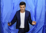 FILE - In this Sunday, April 21, 2019 file photo, Ukrainian comedian and presidential candidate Volodymyr Zelenskiy leaves a booth at a polling station during the second round of presidential elections in Kiev, Ukraine. Volodymyr Zelenskiy, who takes the presidential oath on Monday May 20, 2019, comes into the post having never held political office; his popularity is rooted in playing the role of president on a television sit-com. (AP Photo/Vadim Ghirda, File)