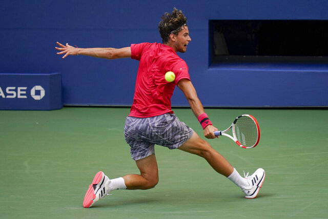 Dominic Thiem, of Austria, returns a shot to Felix Auger-Aliassime, of Canada, during the fourth round of the US Open tennis championships, Monday, Sept. 7, 2020, in New York. (AP Photo/Seth Wenig)