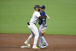 San Diego Padres' Fernando Tatis Jr. (23) hugs Seattle Mariners shortstop Dylan Moore (25) after hitting a double during the third inning of a baseball game Saturday, Sept. 19, 2020, in San Diego. (AP Photo/Denis Poroy)