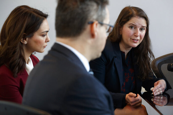 Nazanin Boniadi, left, an actress and activist, listens as Sarah Moriarty, the daughter of Robert Levinson, a U.S. hostage in Iran, speak about her father's captivity, Tuesday, Dec. 3, 2019, in Washington. At front is international human rights lawyer Jared Genser. (AP Photo/Jacquelyn Martin)