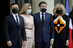 French President Emmanuel Macron, second right, and his wife Brigitte Macron, right, pose with Ukrainian President Volodymyr Zelenskyy, left, and Olena Zelenska before a working lunch at the Elysee palace in Paris, Friday, April 16, 2021. Ukrainian President Volodymyr Zelenskyy is holding talks with French President Emmanuel Macron and German Chancellor Angela Merkel amid growing tensions with Russia, which has deployed troops at the border with the country. (AP Photo/Lewis Joly)